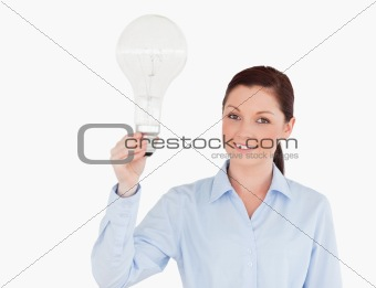 Attractive red-haired woman holding a bulb while standing