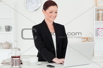 Attractive red-haired woman in suit relaxing with her laptop in