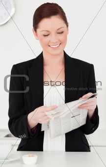 Beautiful red-haired woman in suit reading the newspaper in the