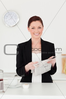 Attractive red-haired woman in suit reading the newspaper in the