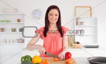 Beautiful red-haired woman cutting some vegetables in the kitche