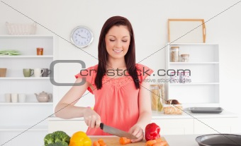 Attractive red-haired woman cutting some vegetables in the kitch