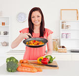 Gorgeous red-haired woman cooking vegetables in the kitchen