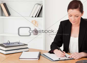Attractive red-haired woman in suit writing on a notepad