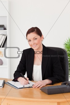 Beautiful red-haired woman in suit writing on a notepad and posi