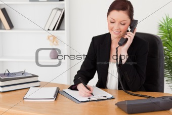 Beautiful red-haired woman in suit writing on a notepad and phon