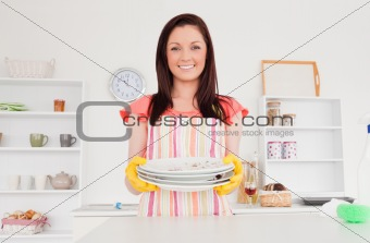 Beautiful red-haired woman posing while holding some dirty plate