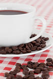 Coffee, saucer and beans on a tablecloth