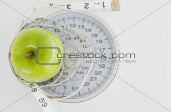 Green apple circled with a tape measure and weigh-scale