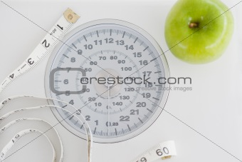 Top view of a green apple along with a tape measure and a weigh-