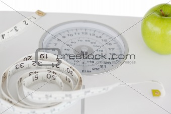 Green apple with a tape measure and a weigh-scale