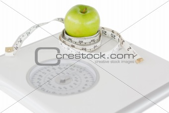 Green apple circled with a tape measure and a weigh-scale