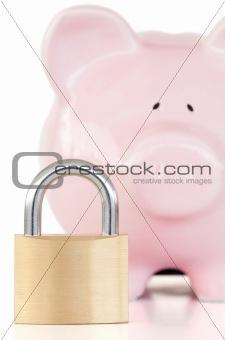Close up of a pink piggy bank and padlock