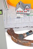 Toy house model with hammer and helmet on a plan