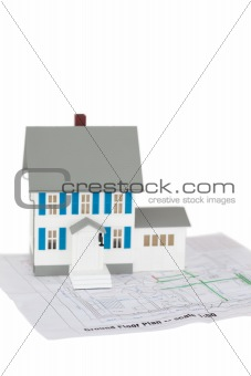 Grey toy house model on a ground floor plan