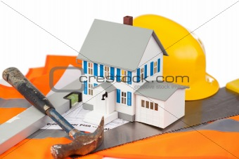 Tools and miniature house on an orange jacket