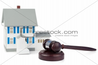 Grey toy house model and brown gavel