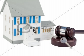Grey toy house model with a key and a brown gave