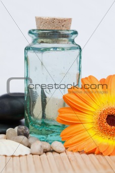 A glass flask with round smooth pebbles and a sunflower