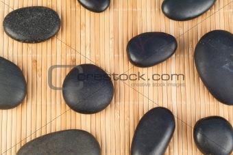 Black stones against bamboo background