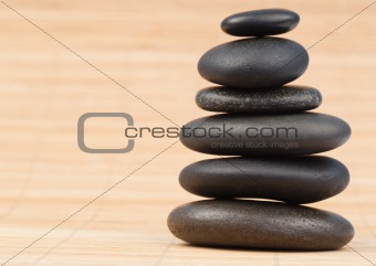 Black stones stack against bamboo background