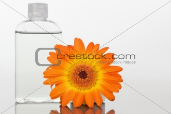 Close up of a glass flask and an orange gerbera on a mirror