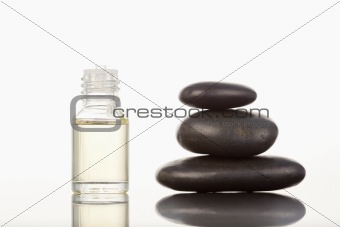 Black pebbles stack and a glass phial