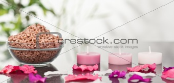 A bowl of brown gravel with pink petals and candles