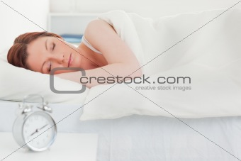 Beautiful red-haired woman sleeping in her bed