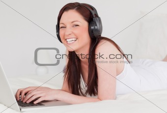 Attractive red-haired female relaxing with her laptop and her he
