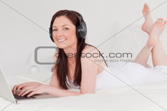 Beautiful red-haired female relaxing with her laptop and her hea