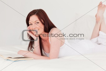 Good looking red-haired woman reading a book while lying on her