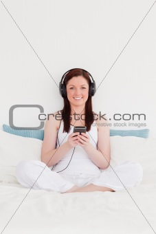 Beautiful red-haired woman listening to music with her headphone