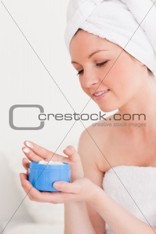 Beautiful young woman wrapped in a towel using skin cream