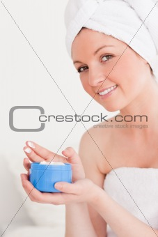Attractive young woman wearing a towel using skin cream