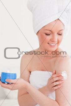 Cute young woman wearing a towel using skin cream