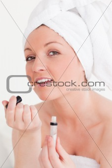 Beautiful young woman wearing a towel using a lip gloss