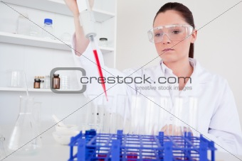 Attractive female biologist holding a manual pipette with sample