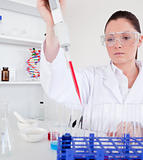 Gorgeous female biologist holding a manual pipette with sample f