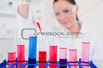 Attractive red-haired scientist filling up a test tube