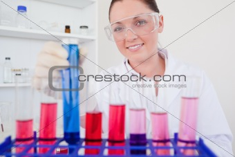 Beautiful red-haired female holding a test tube