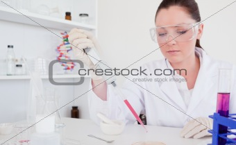 Beautiful red-haired scientist using a pipette