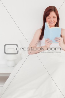 Attractive red-haired female reading a book while sitting on her