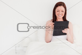 Beautiful red-haired woman relaxing with her tablet while sittin