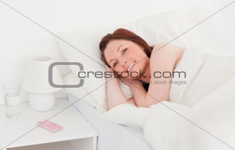 Attractive red-haired woman relaxing while lying on her bed