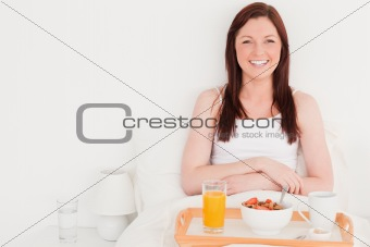 Beautiful red-haired woman having her breakfast while sitting on