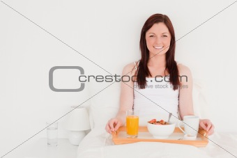 Attractive red-haired woman having her breakfast while sitting o