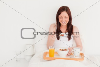 Beautiful red-haired female having her breakfast while sitting o