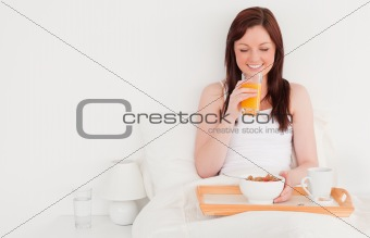 Beautiful red-haired female drinking a glass of orange juice whi
