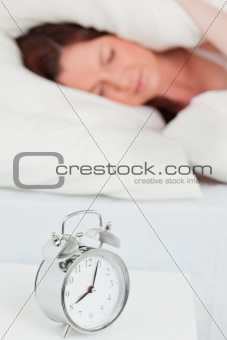 Attractive red-haired female sleeping in her bed